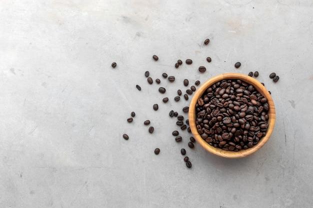 机の背景に木製のカップのコーヒー豆