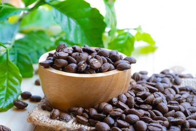 Кофейное зерно, обжаренное в деревянной миске с листом.