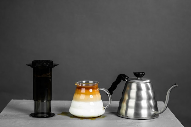 Coffee bean mixing machine and stainless steel kettle with long spout for brewing coffee by hand.