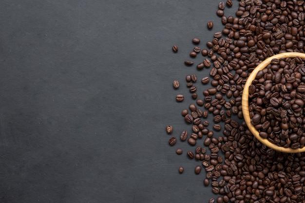 Кофейное зерно на фоне черного деревянного пола. вид сверху. место для текста