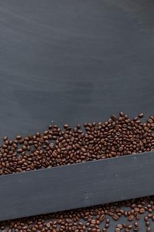 黒い木の床の背景にコーヒー豆。上面図。テキスト用のスペース