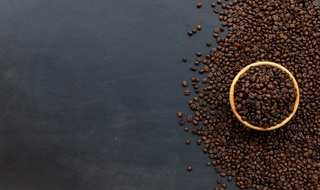 黒い木の床の背景にコーヒー豆