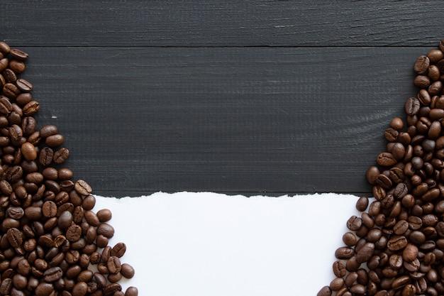 白い紙と黒い木製の背景にコーヒー豆。上面図