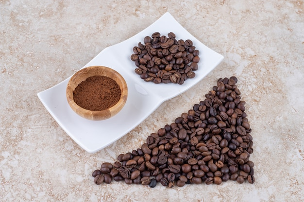 Coffee bean piles and a small bowl of ground coffee