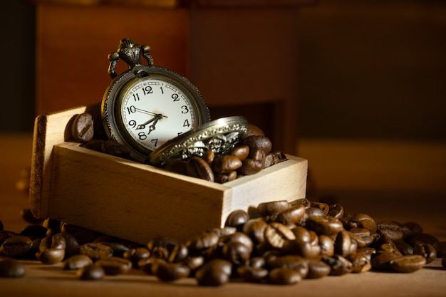 Coffee bean and pocket watch in manual grinder on table. closeup and copy space. concept of coffee time in morning.