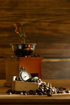 Coffee bean and pocket watch. manual grinder on table in morning.