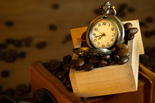 Coffee bean and pocket watch in manual grinder on table.