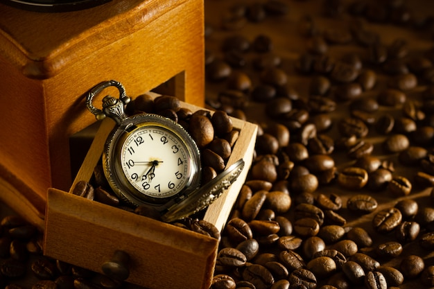 Coffee bean and pocket watch the tray of manual grinder on table. concept of coffee time in morning.