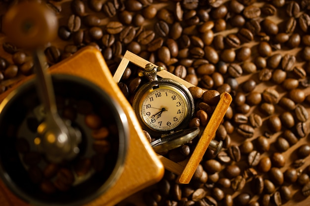 Coffee bean and pocket watch the tray of manual grinder on table.
