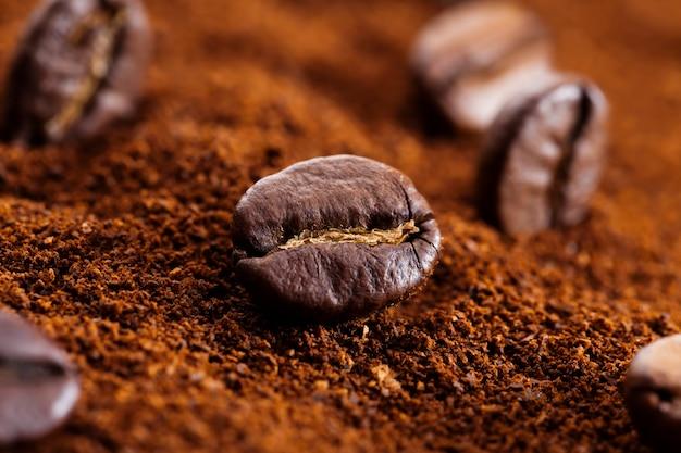 커피 콩 가루, 전체 커피 콩, 볶은 커피 콩이 분쇄된 커피 위에 놓여 있습니다.