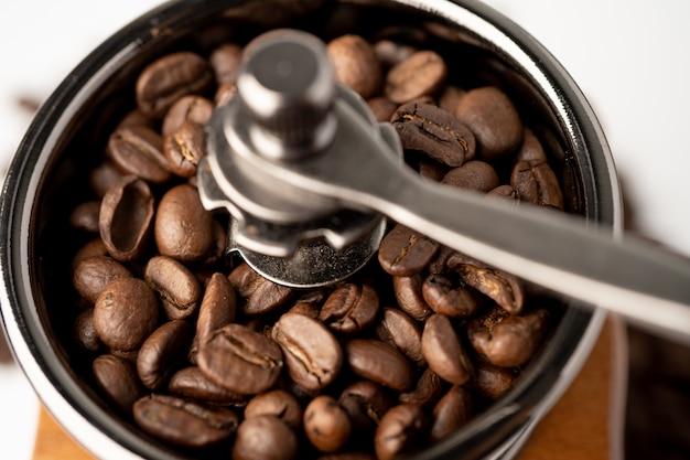 白い背景の上の木製のグラインダーで焙煎したコーヒー豆。