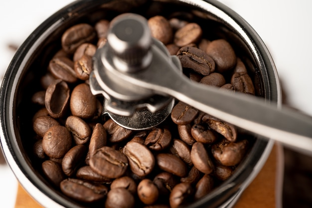 Coffee bean roasted in wooden grinder on white background.