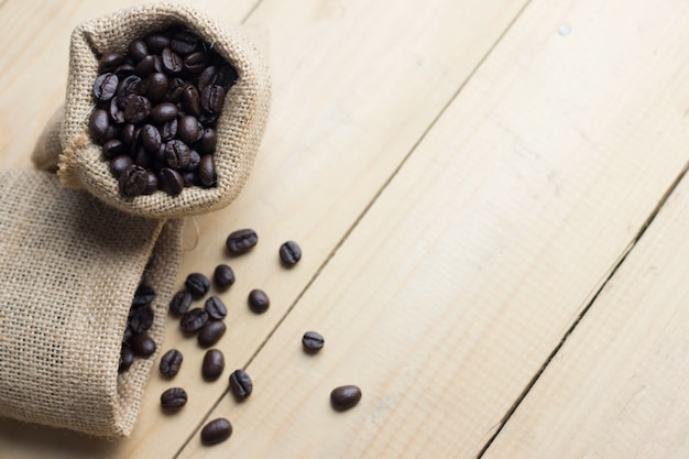 Coffee bean in sack on wooden table. high angle view