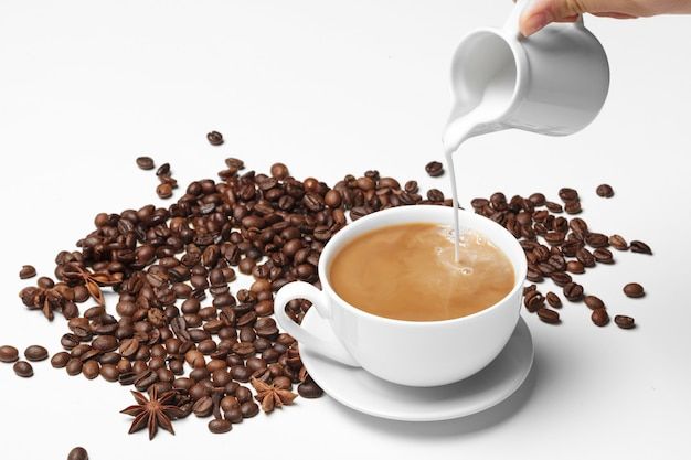 Кофейное зерно маленькая чашка полная кофейных зерен, изолированных на белом