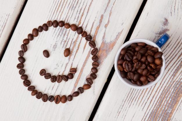 커피 빈 웃는 얼굴과 가득한 컵. 흰색 나무 표면.