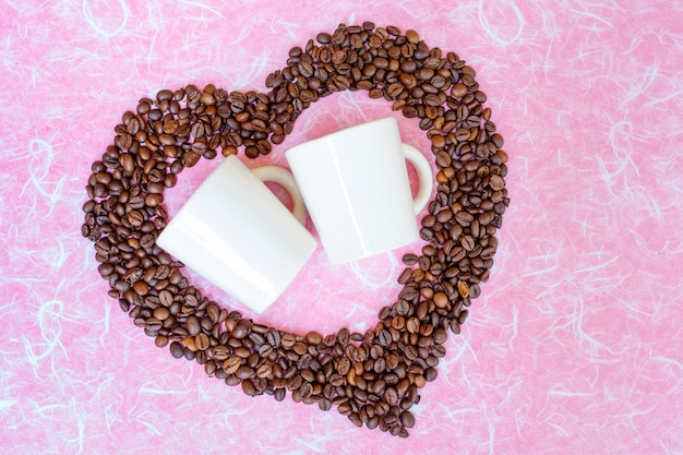 Coffee bean and two white cups on white pink background. top view with copy space.