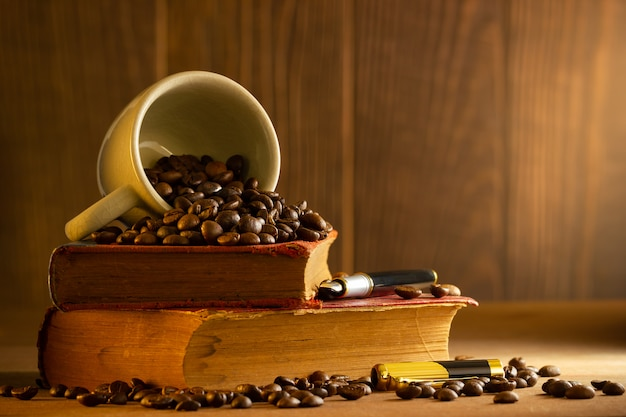 Coffee bean in the white cup and vintage book stacking on wooden table in morning light.