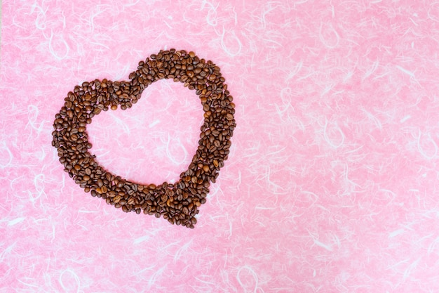 Coffee bean on white pink background. top view with copy space.