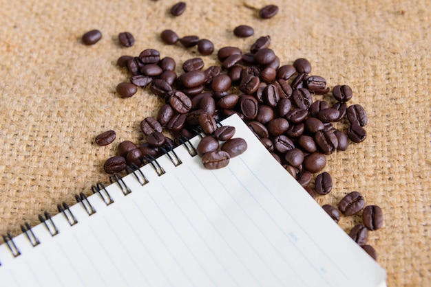 Coffee bean with notebook on burlap background