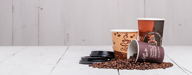 Coffee bean with paper cup on wood background