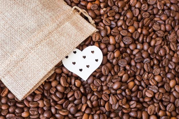 コーヒー豆とキャンバスバッグの近くの心。コーヒーが大好き