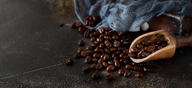 暗い背景の上のコーヒー豆と木のスプーンがクローズアップ