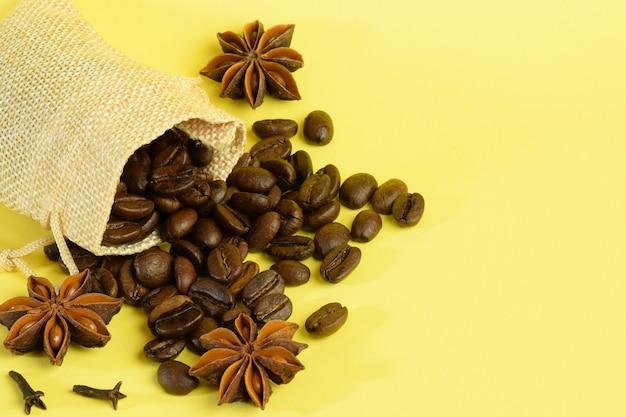 左側の黄色い背景に小さな袋から散らばったコーヒー豆とアニス。