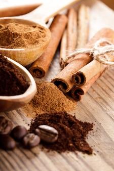 コーヒー豆とシナモンは木製のスプーンでクローズアップを粉砕