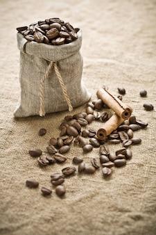 Кофейные зерна и корица на мешковине