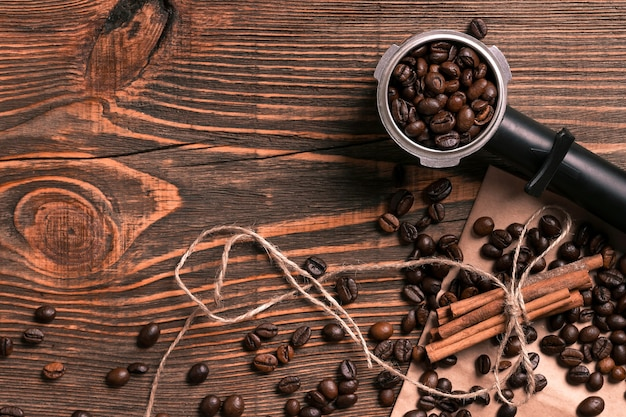 素朴な木製のテーブルにコーヒー豆とシナモンスティック、テキスト用のスペースを上から見たところ。静物。モックアップ。フラットレイ