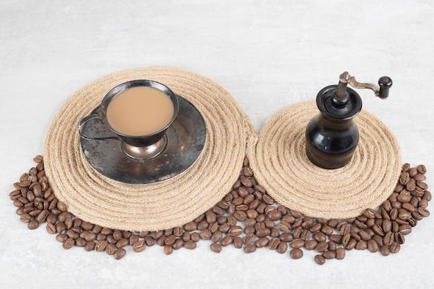 大理石の表面にコーヒー豆とコーヒーグラインダー