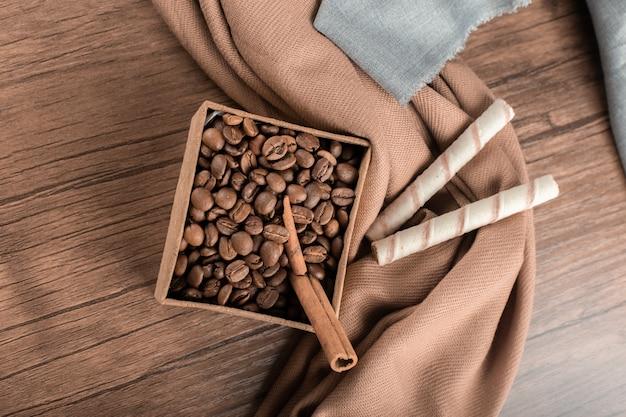 Кофейные зерна и connamons на коробке на деревянном столе