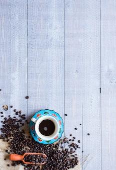 コーヒー豆と別の木製の背景に他のコンポーネントとコーヒーのカップ。テキスト用の空き容量