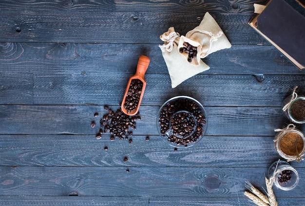 コーヒー豆と別の木製の背景に他のコンポーネントとコーヒーのカップ。