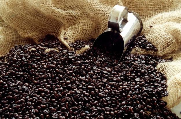 커피 원두와 백그라운드에서 컵 숟가락입니다.