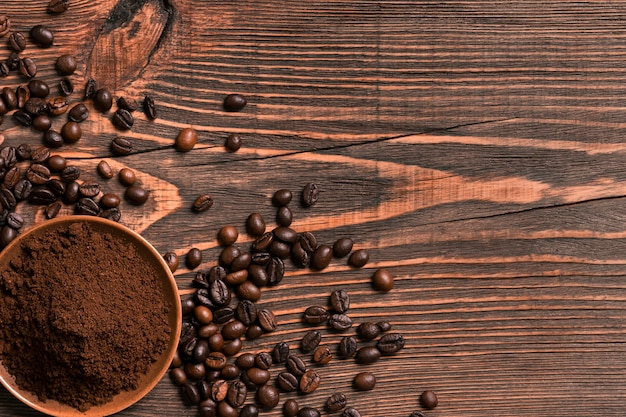 素朴な木製のテーブルにコーヒー豆と挽いたコーヒー、テキスト用のスペースを上から見たところ。静物。モックアップ。フラットレイ