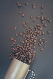 Кофейные зерна и молотый порошок на черном столе. вид сверху с копией пространства