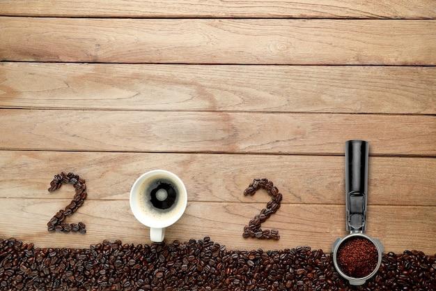 Кофейные зерна и горячий кофе в белой чашке и текст 2021 для happy new year concept.