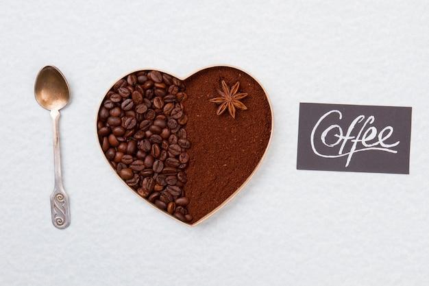 Кофейные зерна и растворимый кофе в форме сердца. серебряная чайная ложка. изолированные на белой поверхности