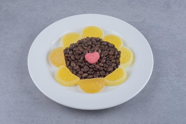 大理石の表面の大皿にコーヒー豆とマーマレード