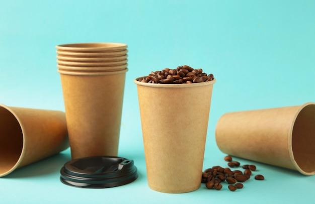 青い背景の上のコーヒー豆と紙のコーヒーカップ。上面図。