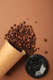 茶色の背景にコーヒー豆と紙のコーヒーカップ。上面図。