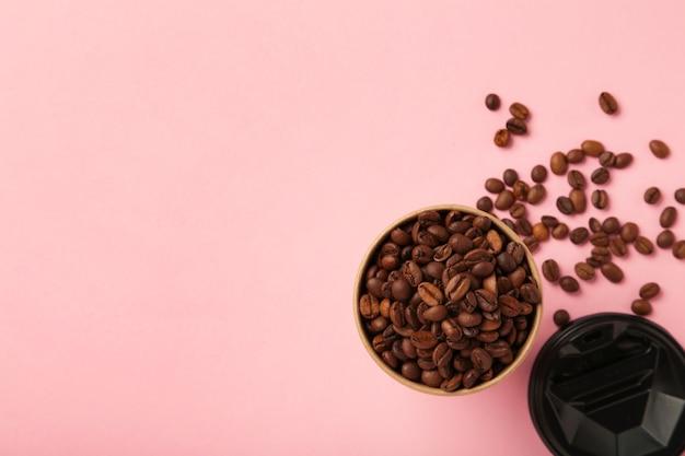 ピンクの背景にコーヒー豆と紙のコーヒーカップ。上面図。