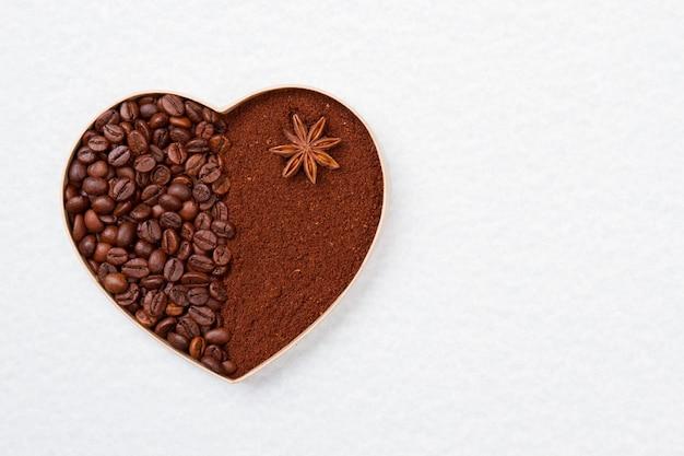 Кофейные зерна и порошок в форме сердца. изолированные на белой поверхности