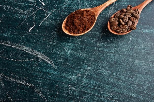 Кофейные зерна и порошок в деревянных ложках.