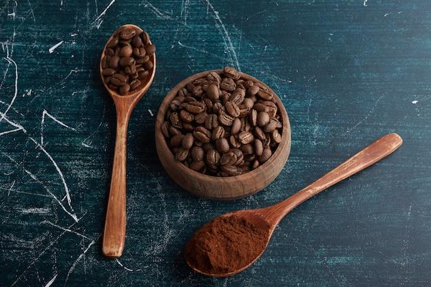 木のスプーンでコーヒー豆と粉末。