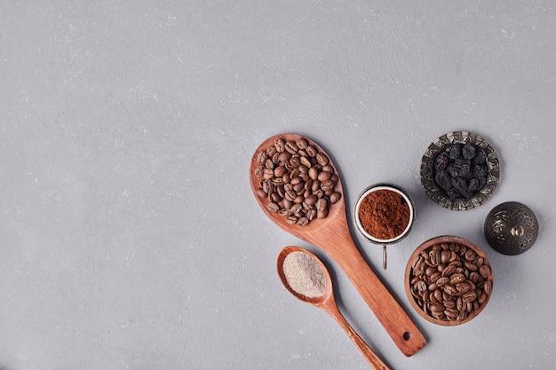 Кофейные зерна и порошки в деревянных ложках.