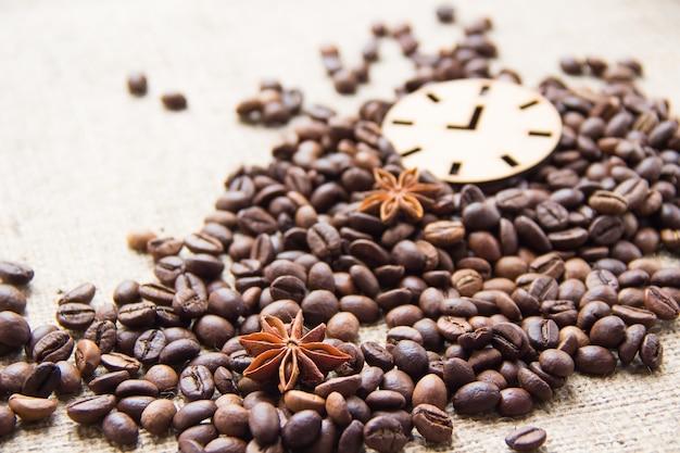 Кофейные зерна и звездчатый анис рассыпаны по столу. значок часов