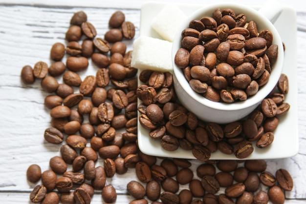텍스트를 위한 나무 배경 카피스페이스에서 아침 식사를 요리하기 위한 커피 콩과 설탕 큐브