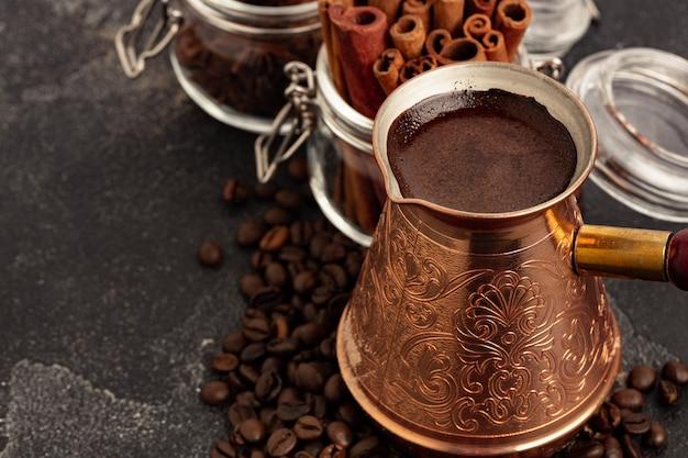 Кофе в зернах и турок на темной поверхности